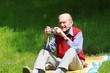 Alter Mann beim Fotografieren auf grüner Wiese