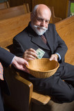 Senior Man Putting Money into Church Basket poster