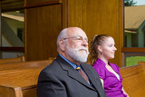 Senior Caucasian Man and Young Woman Sitting in Church Pew poster