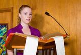 Young Caucasian Woman Reading Bible Church Lectern poster