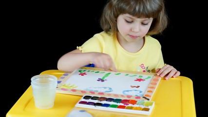 Little girl painting with watyercolors