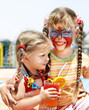 Children with face painting drinking  juice.