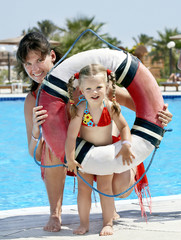 Child with mother near swimming pool.