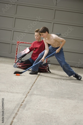 Boys Playing Hockey On Driveway
