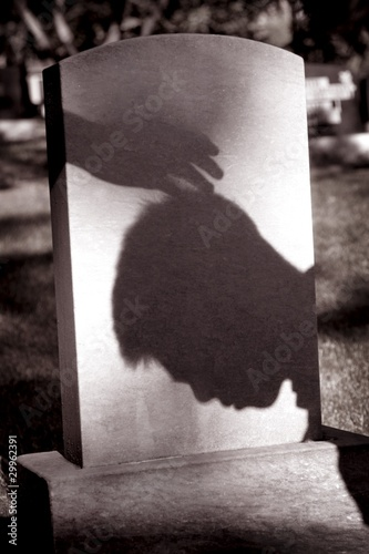 Shadow Of Hand Over Head Of Grieving Man At Grave Site