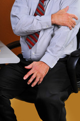 Businessman feeling pain in his left arm sitting at his desk
