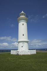 White Lighthouse stands out against green grass and blue sky.