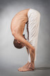 Handsome young man in yoga position. Studio portrait over gray