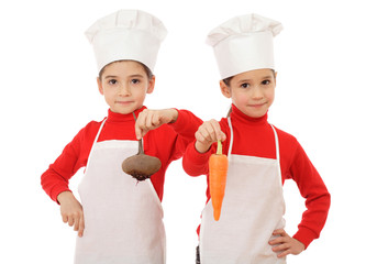 Two little chief-cookers holding a vegetables