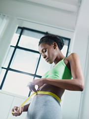 african woman measuring waist with yellow tape