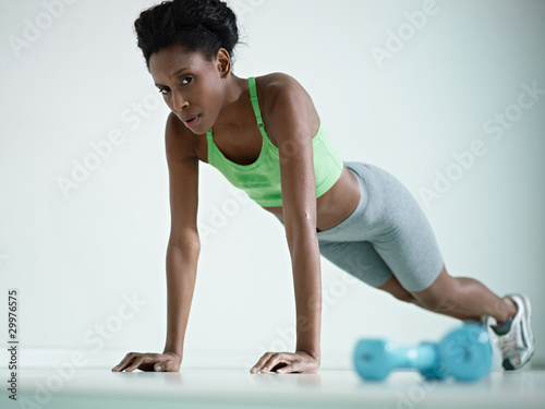 african woman doing series of push-ups in gym