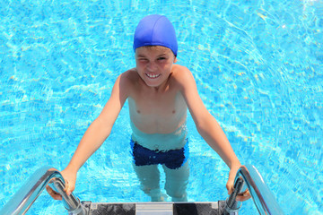 Boy in blue little cap and melting entering in water in pool