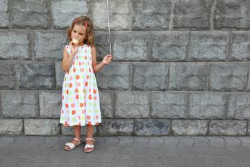 Little girl in  white sarafan eats an ice-cream