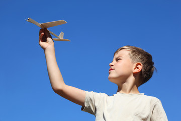 Boy in summer plays with  home-made model of airplane
