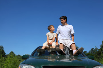 Father and son sit on roof of car in day and look on each other