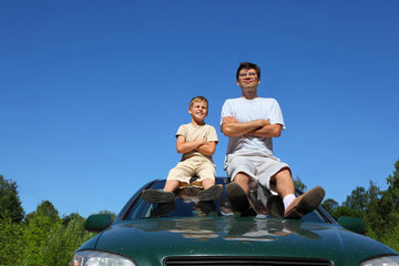 Father with  son of sit on   roof of car in   day and peep