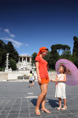 Young mother and little daughter standing on Piazza Popolo