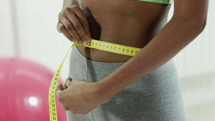 Young black woman measuring waist in gym