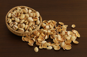 Pistachios in interwoven bowl with spilled nutshells on dark woo
