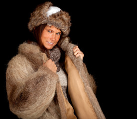 young woman in a fur coat and hat, black background