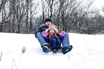 father and daughter riding on a sledge