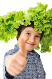 Kid with salad as a hat or wig on his head, thumb up, concept