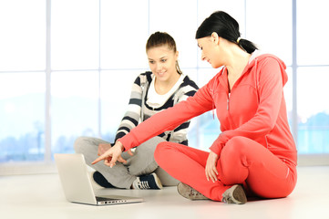 Two girls doing yoga and fitness using laptop in bautiful room