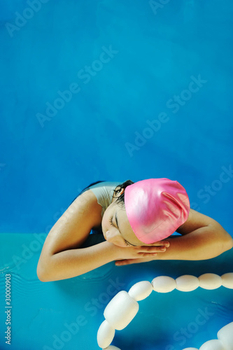 Little kid girl is swimming on pool, large copy-space above