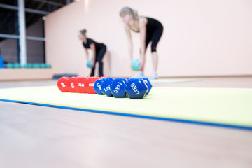 Red and blue dumbbells in a hall for sports trainings
