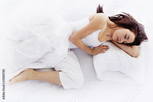 Young woman sleeping on white bed - 30001785