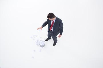 Businessman throwing crumpled paper into wastebasket