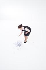 Businesswoman throwing crumpled paper into wastebasket