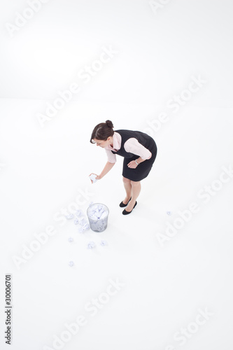 Businesswoman throwing crumpled paper into wastebasket