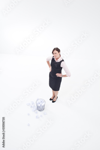 Businesswoman standing at wastebasket with crumpled paper