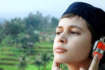 Junge mit Kopfhörer vor tropischem Hintergrund