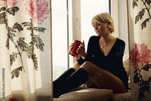 Portrait of charming girl sitting on windowsill and looking thro