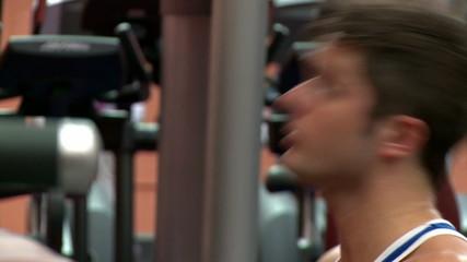 Dark-haired man doing sport bodybuidling