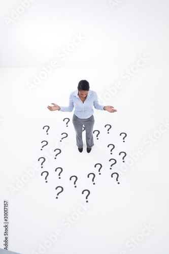 Confused businesswoman surrounded by question marks
