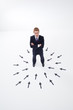 Businessman surrounded by arrows