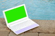 Laptop with green screen near to swimming pool