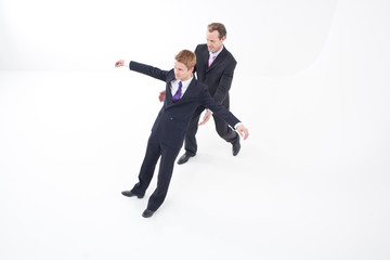 Businessman catching falling colleague