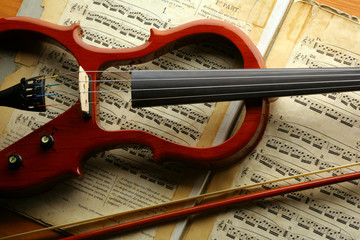 electric violin with violin bow on a sheet music