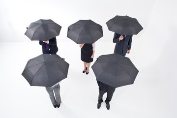 Five businesspeople standing under umbrellas