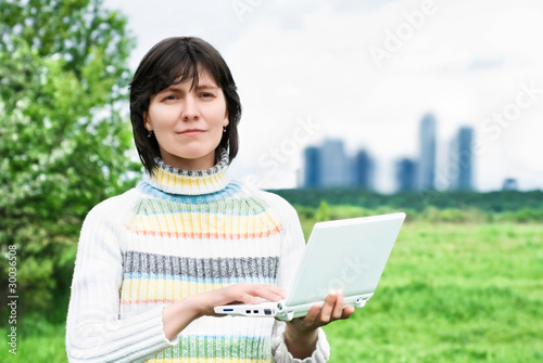 Smiling woman with a laptop on the background of the city buildi