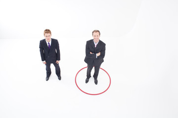 Two businessmen standing inside and outside hoop
