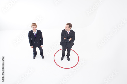 Businessman standing inside hoop smiling at colleague