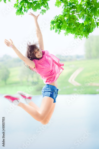Happy girl jumping against the lake