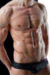 Wet muscular man torso on black white background