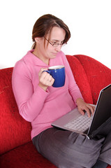 Young woman sitting on red couch with laptop and mug