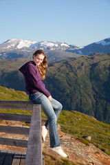 The young girl has a rest on a parapet in mountains